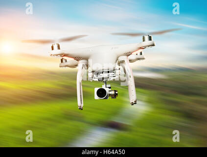 Drone flying above green field in blur motion - Stock Photo