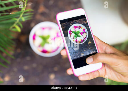 Woman taking picture of tropical fruit salad with cell phone, close-up - Stock Photo
