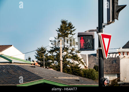 red walk light signal on semaphore with give away sign - Stock Photo