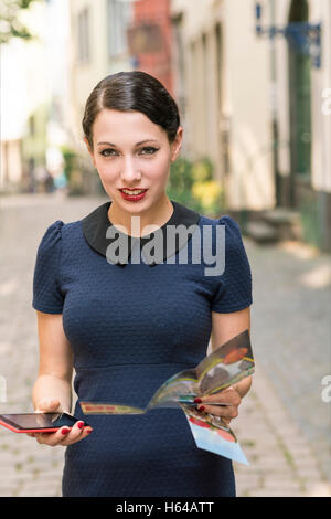 Young woman holding cell phone and flyer in the city - Stock Photo