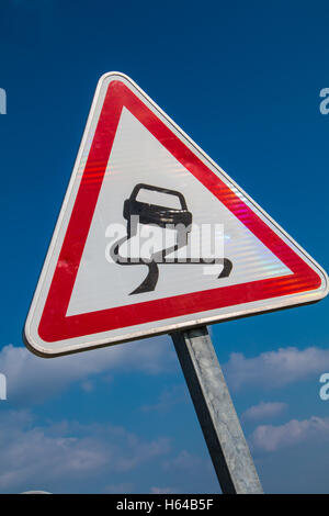 Slippery Road Warning Sign on blue sky - Stock Photo