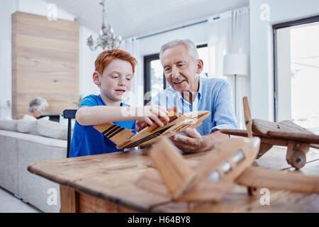 Grandfather and grandson building up model airplanes - Stock Photo