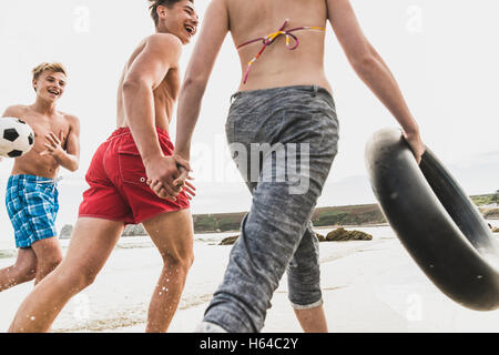 Friends running with a ball and tyre on the beach - Stock Photo