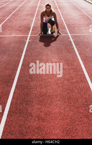 Young woman on tartan track in starting position - Stock Photo