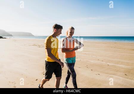 France, Crozon peninsula, sportive young couple walking on the beach - Stock Photo