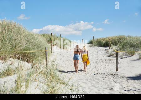 Two female friends walking through dunes leaving beach - Stock Photo