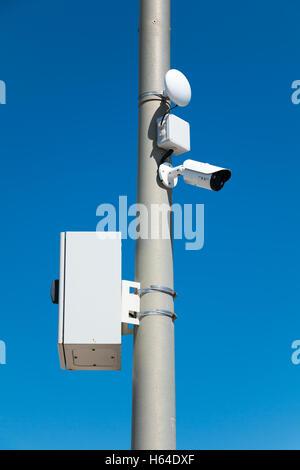 security cameras on street pylon with blue sky - Stock Photo