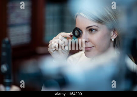 Patient at optometrist trying different lenses - Stock Photo