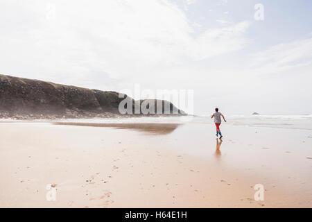 Mature woman running on the beach - Stock Photo