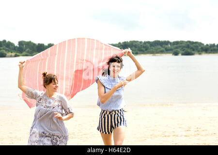 Two happy friends running side by side on the beach holding cloth - Stock Photo