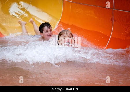Two boys having fun on water slide - Stock Photo