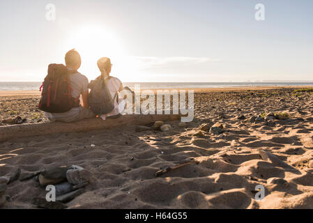France, Bretagne, Finistere, Crozon peninsula, couple during beach walk, sitting on beach, enjoying sunset - Stock Photo