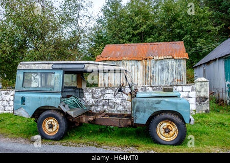 Old rusting abandoned vehicle with peeling paint and no doors sits in front of derelict outbuildings and trees - Stock Photo