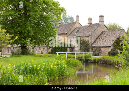 Row of stone houses near wooden bridge over small river in rural English village on overcast day - Stock Photo