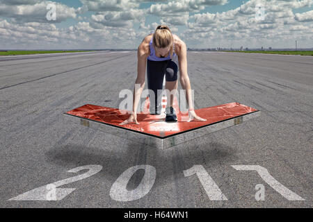 Female runner kneels in start position on a red floating arrow platform, which is placed above an airport runway - Stock Photo