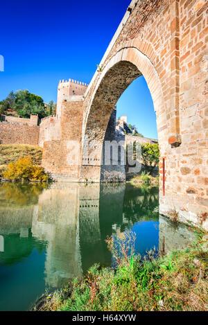 Toledo, Spain. Alcantara Bridge ( Puente de Alcantara ) is an arch bridge in Toledo, Spain, spanning the Tagus River. - Stock Photo