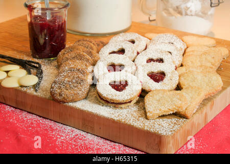 Christmas cookies on a wooden board with jam and a jar of baking powder. - Stock Photo