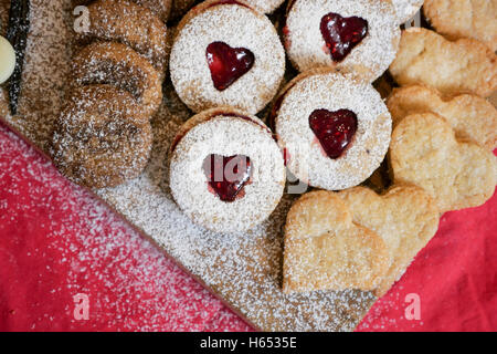 cookies and biscuits presented on a wooden board with ingredients next to it - Stock Photo