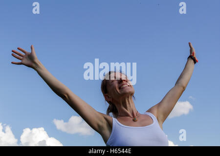 a young woman raise or stretches her hands towards the sky - Stock Photo