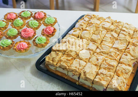 a cheese cake on a plate and muffins, cupcakes decorated - Stock Photo