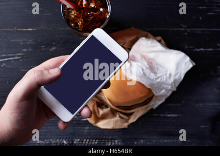 Cheeseburger with moblie phone - Stock Photo