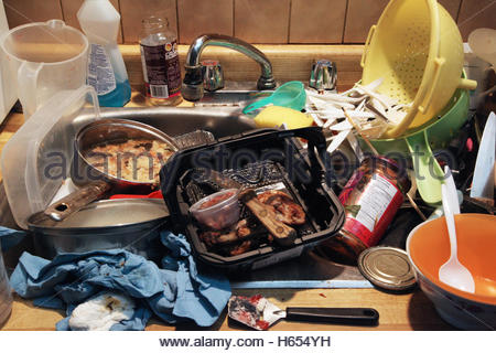 Dirty dishes with old food piled in a sink in a messy kitchen. - Stock Photo