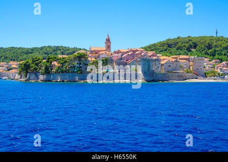KORCULA, CROATIA - JUNE 25, 2015: View of old city from the sea, with city walls and towers, the cathedral, locals - Stock Photo