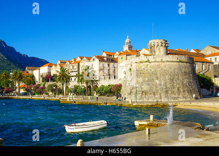 KORCULA, CROATIA - JUNE 25, 2015: Scene of the western side of the old town, with houses, boats, locals and visitors, - Stock Photo