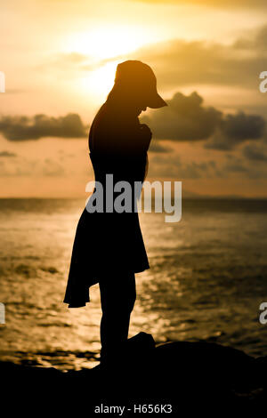 woman standing wear a cap with sunset silhouette - Stock Photo