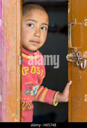 Ladakh, India - August 17, 2015: Young ladakhi girl behind door in Thardot Choeling Nunnery. - Stock Photo