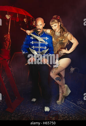 Cabaret performers, one holding swords - Stock Photo