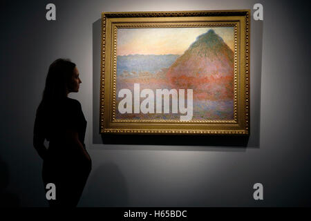 London, UK. 24th Oct, 2016. A Christie's employee poses with impressionist artist Claude Monet's artwork 'Meule' - Stock Photo