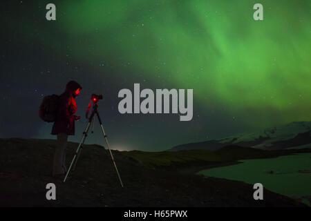 A photographer photographing the Aurora at Jokulsarlon Iceberg Lagoon, Vatnajokull National Park, Iceland. - Stock Photo
