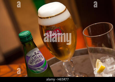 Glass of Stella Artois lager, and Highland Spring water, with ice on a pub tray - Stock Photo