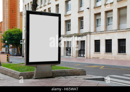 Blank billboard mock up in the street, in front of a building - Stock Photo