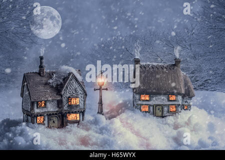 Winter cottages in country lane landscape at night with glowing lamp light - Stock Photo