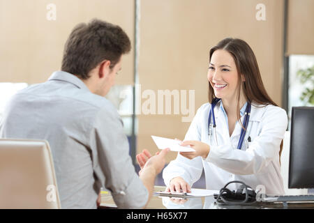 Happy doctor female giving a prescription to her patient in a consultation - Stock Photo