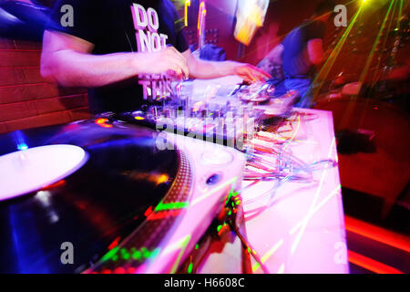 DJ behind the decks in a nightclub. - Stock Photo