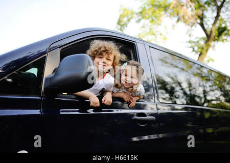children look out from a car window - Stock Photo