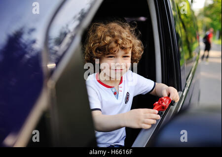 baby boy looks out the car window - Stock Photo