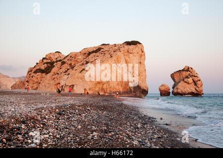 Vacationers near rocks Petra Tou Romiou at sunset, Cyprus - JULY 17, 2015 Petra tou Romiou, also known as Aphrodite's - Stock Photo