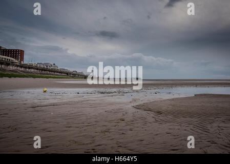 Dark, moody sunset on the beach in Blackpool, England with Blackpool Tower in the background Stock Photo