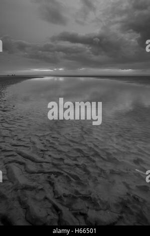 Dark, moody sunset on the beach in Blackpool, England during autumn while the famous Black Illuminations are lit up Stock Photo