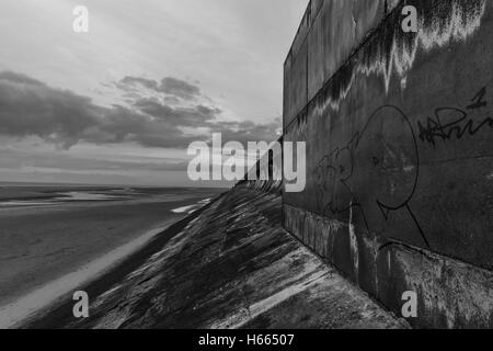 Dark, moody sea wall at sunset in Blackpool, England during autumn while the famous Black Illuminations are lit up Stock Photo