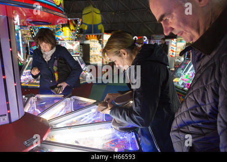 Adults playing in the amusement arcade, Brighton Pier, Brighton, East Sussex England UK - Stock Photo