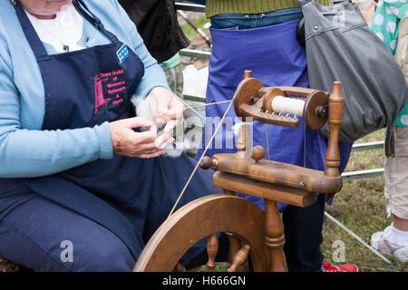 skillful lady using spinning wheel - Stock Photo
