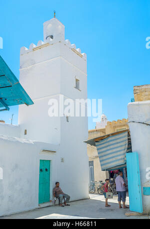 The tiny mosque on the narrow street of Medina built in the same style as residential houses - Stock Photo