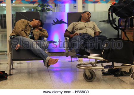 Weary travelers sleep before their flight at Indira Gandhi International Airport in Delhi, India. - Stock Photo