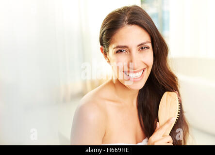 Portrait smiling brunette woman brushing hair - Stock Photo