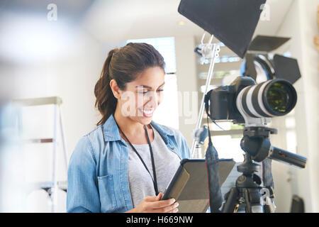 Female photographer using digital tablet behind camera in studio - Stock Photo